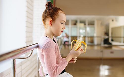 Маленькая балерина ест банан