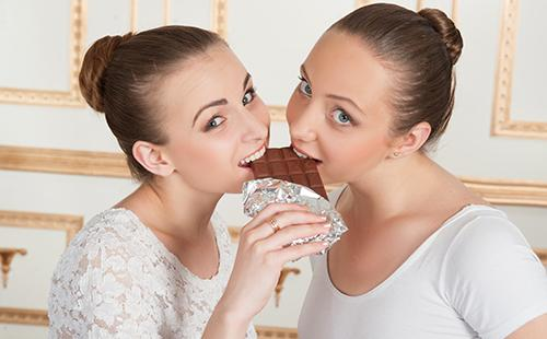 Две балерины кусают плитку шоколада