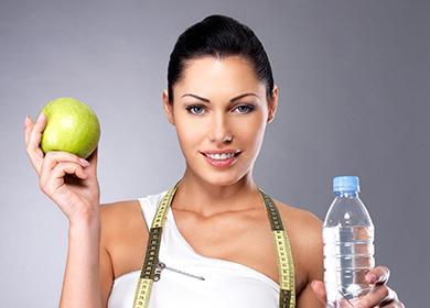 Красивая девушка с зелёным яблоком и бутылкой воды