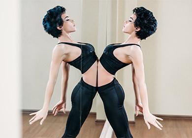 Женщина занимается спортом возле зеркала