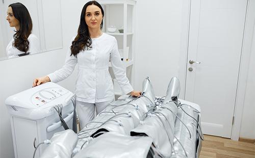 Косметолог выполняет процедуру прессотерапии