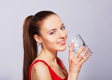 Девушка в красной майке пьёт воду из стакана