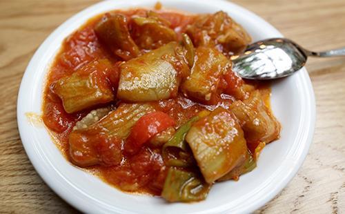 Овощное рагу в тарелке с ложкой