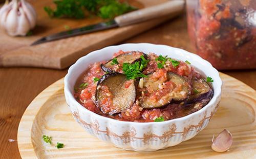 На столе тарелка с баклажанами и томатами