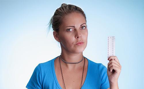 Девушка в синей футболке держит в руках таблетки