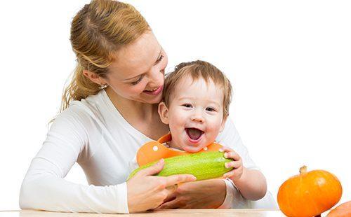 Мать с малышом за столом держат цуккини