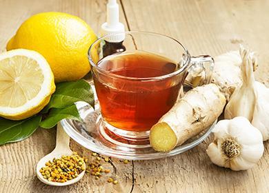 Вокруг чашки разложены лимоны, корень имбиря и чеснок