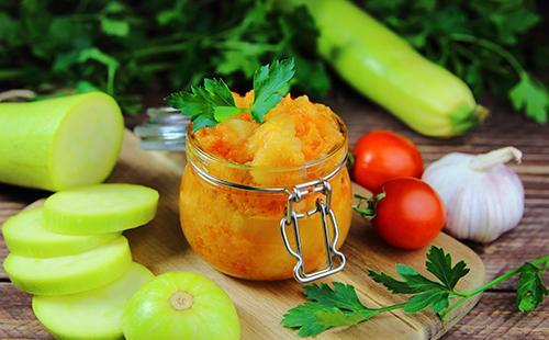 Консервированные овощи в банке, нарезанные кабачки, помидоры черри и петрушка