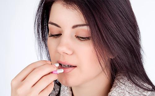 Девушка пьет таблетку