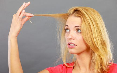 Девушка смотрит на свои волосы
