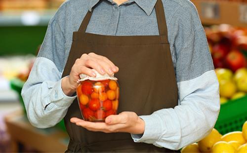 Женщина держит в руках банку с консервированными помидорами