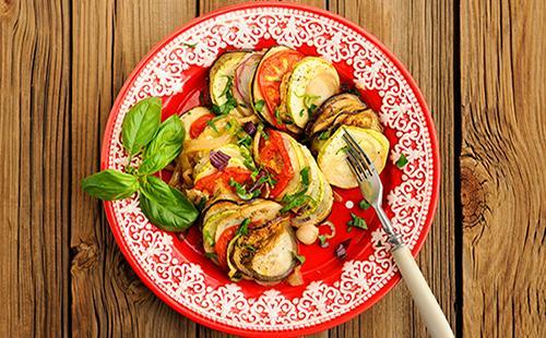 Блюдо на тарелке из баклажанов и помидоров с зеленью