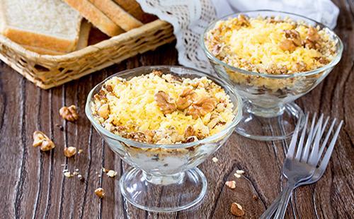 Салат в пиале, посыпанный сыром и и грецкими орехами