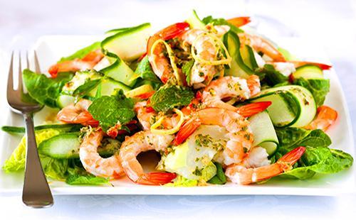 Салат с креветками, огурцами и зеленью на тарелке