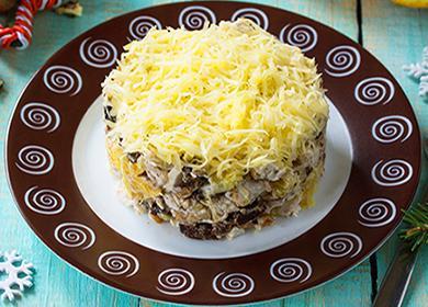 Слоеный салат на тарелке с курицей, черносливом, майонезом и тертым сыром