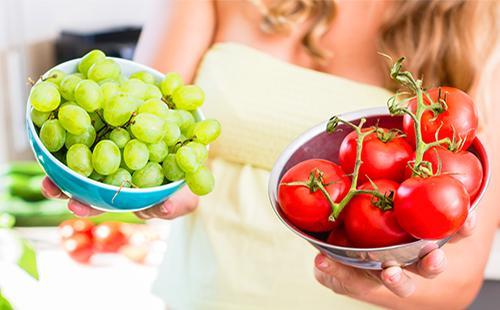 Женщина держит помидоры и виноград в чашках