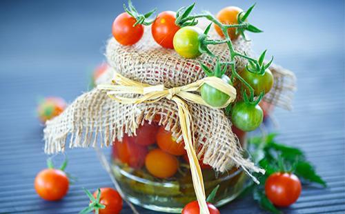 Зеленые и красные помидоры черри в банке