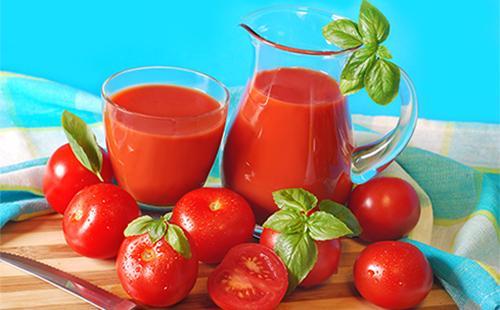 Томатный сок в кувшине и бокале, помидоры и зелень