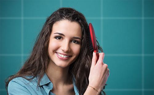 Молодая женщина расчесывает волосы