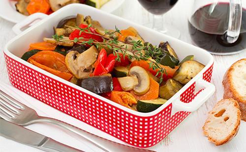 Печеные баклажаны с шампиньонами и морковью на столе