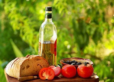 Домашний хлеб, помидоры и бутыль оливкового масла