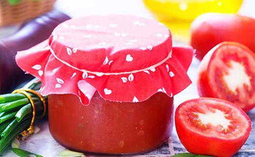 Томатная паста в банке и разрезанные помидоры