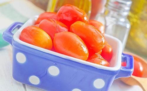 Маринованные помидоры в чаше на столе