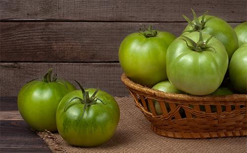 Незрелые помидоры в корзинке