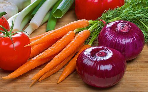Пучок морковки и две фиолетовые луковицы