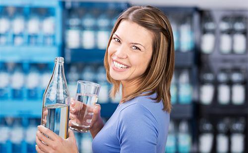 Девушка держит в руках стакан и бутылку минеральной воды