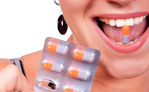 Девушка с улыбкой держит капсулу в зубах