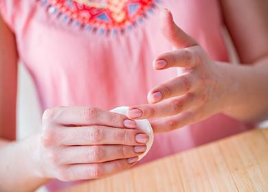 Девушка вытирает ногти ватным диском