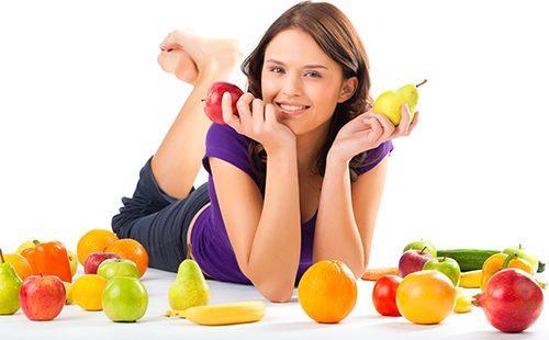 Девушка держит яблоко и грушу