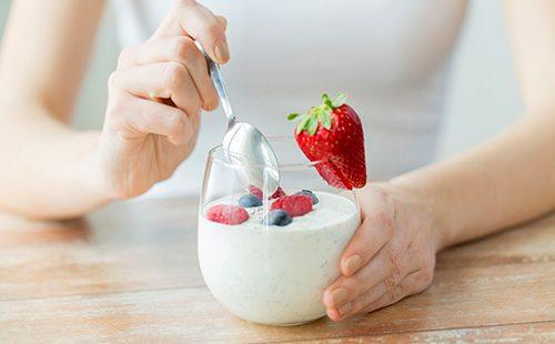 Женщина ест йогурт с ягодами
