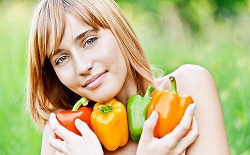 Красивая девушка с разноцветными перцами в руках