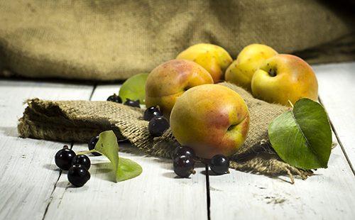 Абрикосы и чёрная смородина на деревянном столе
