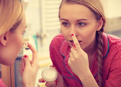 Девушка мажет кремом нос
