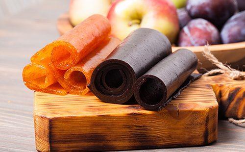 Яблоки, сливы и пастила на доске