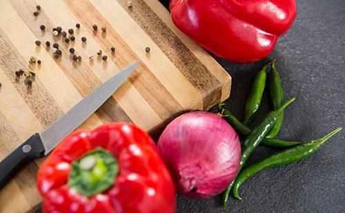 Сладкие перцы, луковица и нож