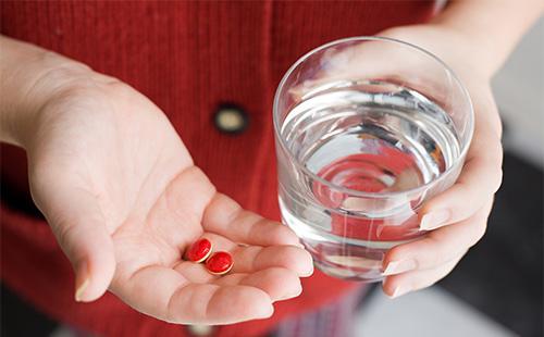 Красные таблетки на ладони