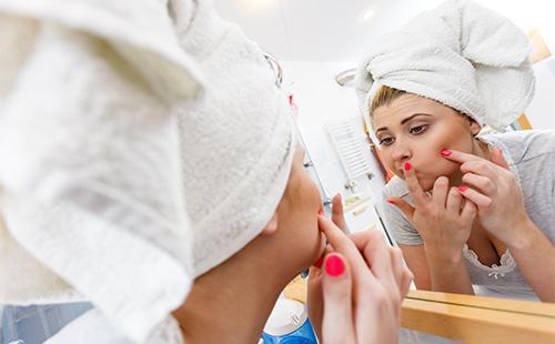 Девушка с полотенцем на голове смотрит в зеркало