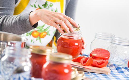Женщина наполняет баночки томатным соусом