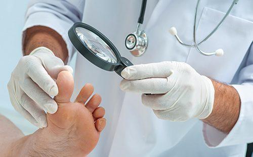 Доктор обследует ногу пациента