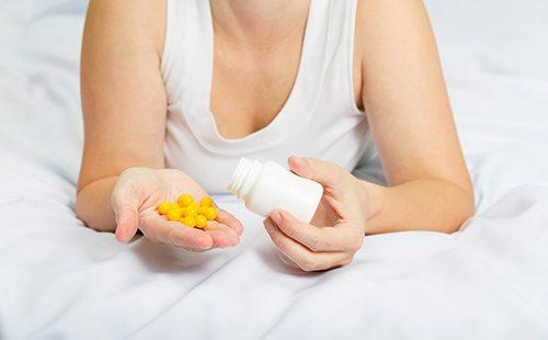 Женщина в постели держит жёлтые таблетки