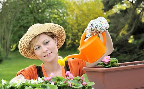 Женщина поливает вазон