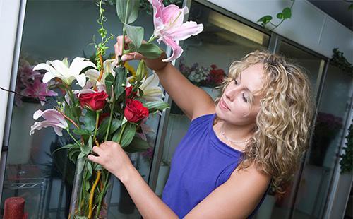 Женщина формирует букет в вазе