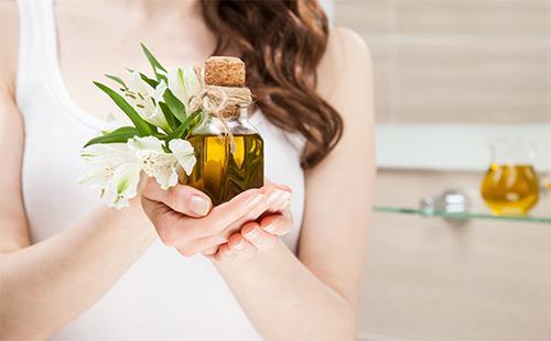 Бутылочка с маслом в руках