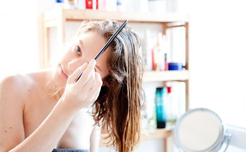 Женщина расчесывает влажные волосы