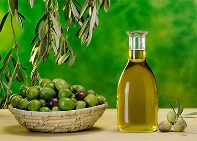 Оливковое масло в бутылке и оливки тарелке