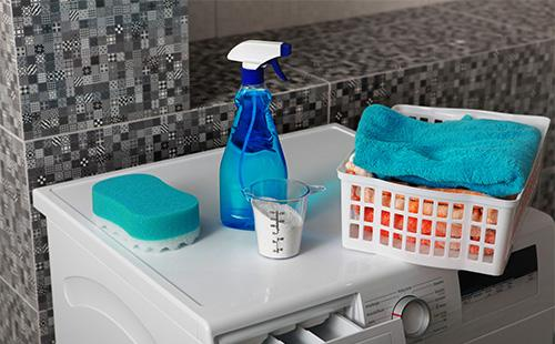 Стиральный порошок и полотенце на стиральной машине